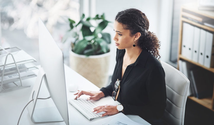 Woman At Desk In Office Doing Market Research