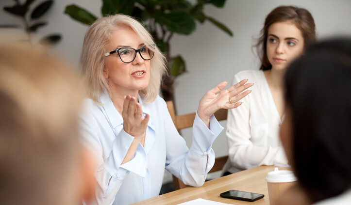 Todays Leaders Need To Embrace Intelligent Enterprise Search. A Blond Woman In Her Fifties With Black Rimmed Glasses Leads A Team Meeting Around A Conference Table.
