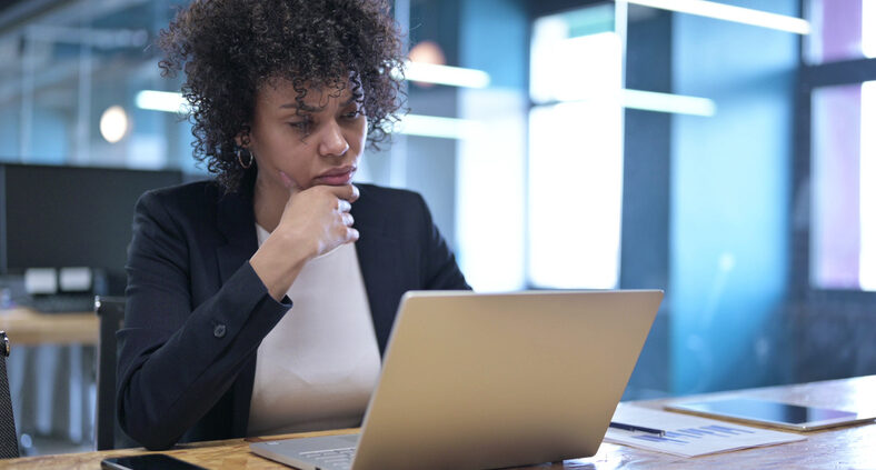 Pre-curated Content Can Have Real ROI For Knowledge Management Users Like The Young Black Professional Woman Working At Her Laptop Pictured Here.