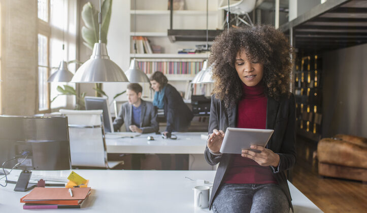 A Black Millenial worker reads from a tablet in a bright office. Can your knowledge management system mitigate the great resignation?